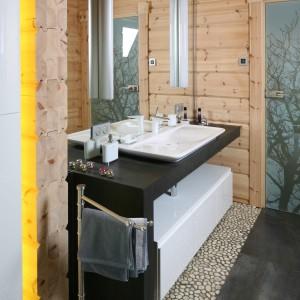 W tej łazience drewniane bala prezentują się w całej swojej okazałości. W połączeniu z bazaltem, otoczakami i armaturą o linearnym kształcie jeszcze bardziej zachwyca swoim naturalnym pięknem.