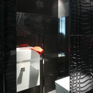 Wysokie lustro zostało umieszczone nie nad, lecz naprzeciw umywalki. W ten sposób nie tylko powiększyło niewielka przestrzeń, ale też poprzez multiplikację białych elementów wyposażenia znacząco ją rozświetliło. Projekt Łukasz Sałek. Fot. Bartosz Jarosz.