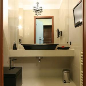 Mała łazienka urządzona została z wielkim przepychem. Odnajdujemy tu zarówno klasyczne elementy wystroju wnętrza - stylową umywalkę czy ciepły beż ścian, jak i całkiem salonowe wyposażenie - kryształowy żyrandol, ozdobna grafika oraz... telewizor. Projekt Piotr Stanisz. Fot. Bartosz Jarosz.