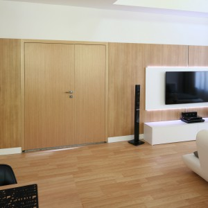 Obecny w całym domu drewnopodobny dekor pojawia się także na głównej ścianie salonu, stanowiąc doskonałe tło dla panelu na telewizor. Świetnie też zamaskował drzwi. Projekt Małgorzata Błaszczak. Fot. Bartosz Jarosz.