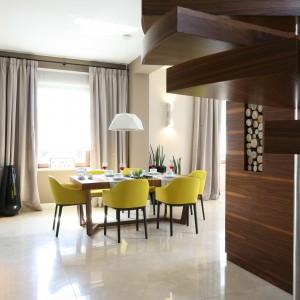 Kolor drewna, będącego istotną ozdobą salonu powtórzono na klatce schodowej, którą ulokowano tuż za ścianką z telewizorem. Monochromatyczną kolorystykę wnętrza przerywają żółte krzesła Vitra.  Projekt Katarzyna Koszałka. Fot. Bartosz Jarosz.