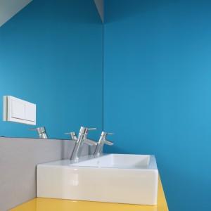 Tafla szkła zamontowana nad umywalkami pięknie odbija żywe kolory, które choć dominują we wnętrzu, to w żadnym stopniu go nie przytłaczają. Projekt Małgorzata Galewska. Fot. Bartosz Jarosz.