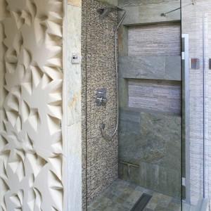 Dzięki zastosowaniu na ścianie prysznica sprowadzonej  z Bali widowiskowej mozaiki z łupanego marmuru oraz dekoracyjnego reliefu nawiązującego do plumerii – typowego kwiatu rosnącego na tej wyspie, wnętrze przypomina bardziej salon spa niż tradycyjną łazienkę. Projekt Karolina Łuczyńska. Fot. Bartosz Jarosz.