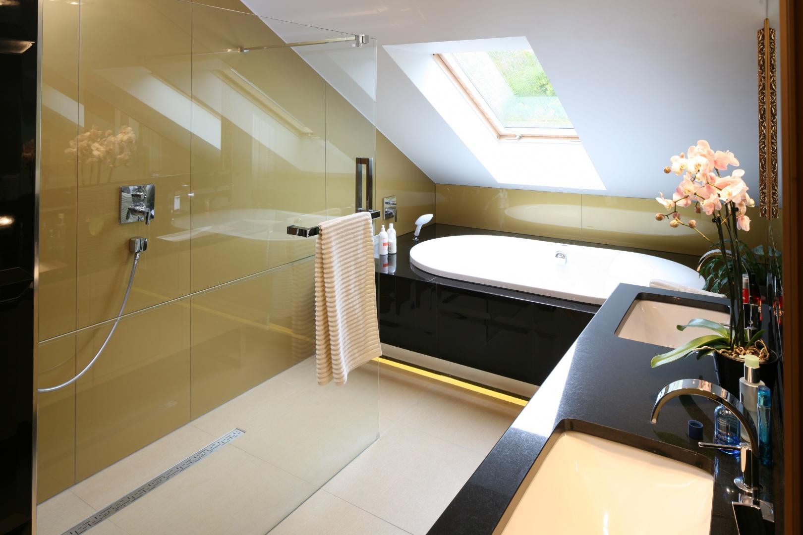 Szklana tafla oddziela prysznic od części z umywalkami, funkcjonalnie dzieląc przestrzeń łazienki. Jest praktycznie niewidoczna, co pozwoliło wyeksponować szkło Lacobel w kolorze złota. Projekt Chantal Springer. Fot. Bartosz Jarosz.