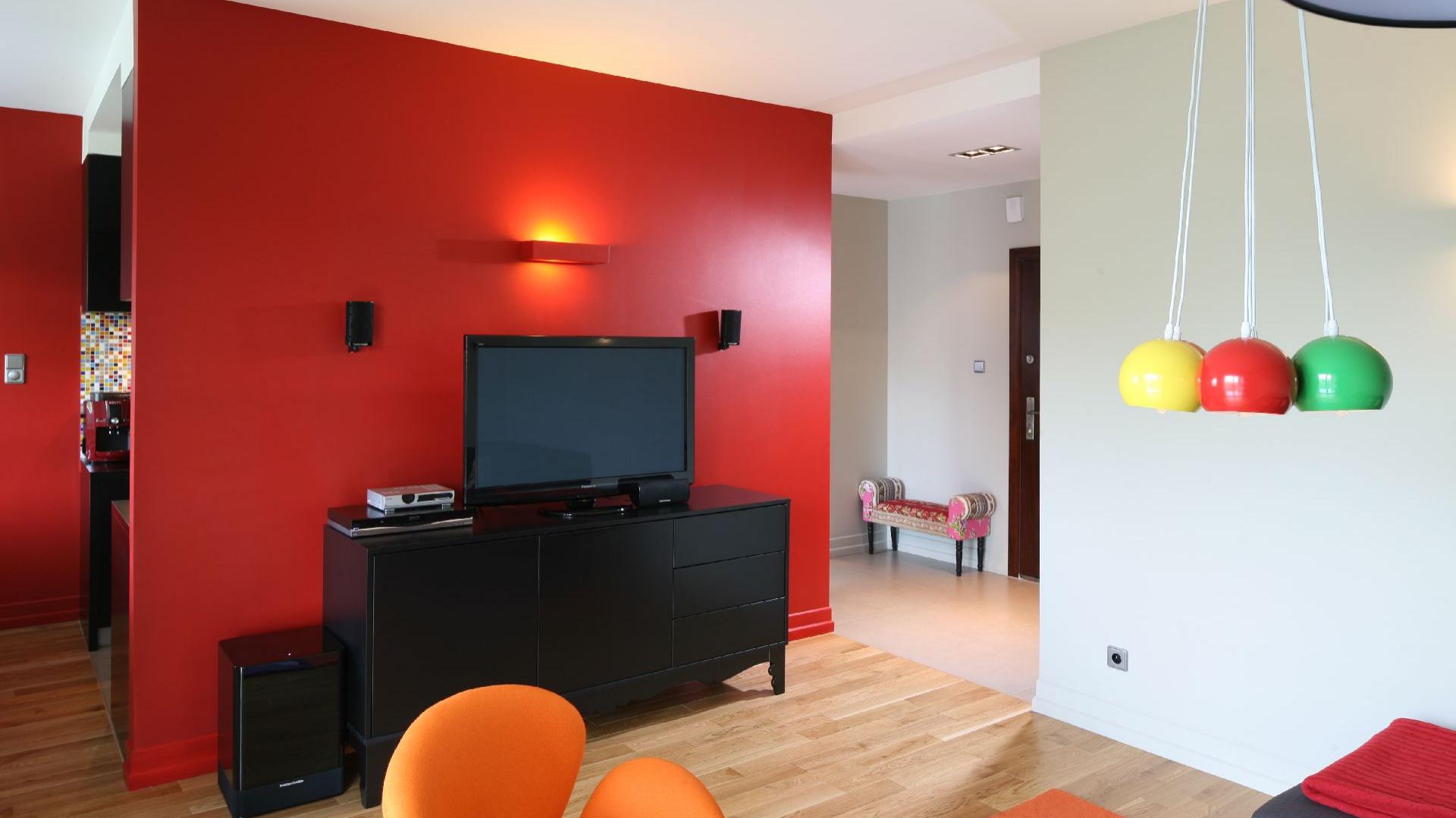 Ognista czerwień zagościła na ścianie telewizyjnej w tym nowoczesnym, pełnym życia mieszkaniu. Proj. wnętrza Dorota Szafrańska. Fot. Bartosz Jarosz.