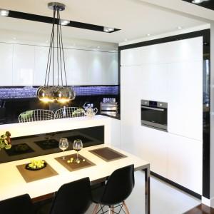 W tej kuchni ścianę nad blatem zabezpieczają dwa różne materiały. Są to tafle czarnego szkła Lacobel połączone z efektowną mozaiką Fat Cube marki Dunin, również w kolorze czarnym. Projekt: Małgorzata Mazur. Fot. Bartosz Jarosz. Stylizacja: Ewa Kozioł.