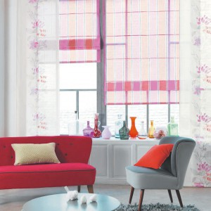 Lekkie zasłony w delikatne kwiaty są świetnym uzupełnieniem różowych rolet. Fot. Casadeco.