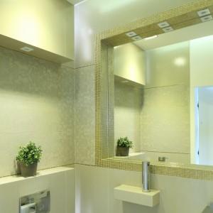 Urządzoną w stylu glamour łazienkę zdobią subtelne dekory płytek oraz złota mozaika zastępująca ramę lustra. Projekt Agnieszka Hajdas-Obajtek. Fot. Bartosz Jarosz.