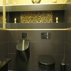 Czarne płytki ułożono na 3/4 ściany. połączono ze złotymi. Aby wnętrze nie było zbyt ciemne połączone je ze złotem. W tym kolorze są nie tylko dekoracje ścienne, ale i sufit. Projekt Maciej Roszkowski. Fot. Bartosz Jarosz.