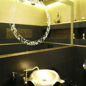 Złota umywalka wraz ze stylizowaną baterią to główna ozdoba toalety przeznaczonej dla gości.  Jej salonowy charakter podkreślają kryształowe kinkiety. Projekt Maciej Roszkowski. Fot. Bartosz Jarosz.