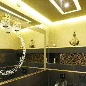 Małą toaletę, przeznaczoną głównie dla gości urządzono z wielkim przepychem. W kolorze złota są tu nie tylko dodatki i akcesoria, ale też ceramika oraz okładziny ścienne. Projekt Maciej Roszkowski. Fot. Bartosz Jarosz.