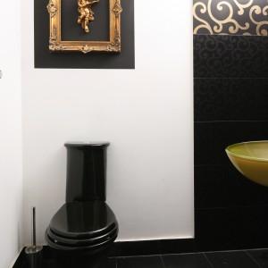 Wzrok osób wchodzących do tej gościnnej toalety przyciąga dekoracja na ścianie vis a vis drzwi - złota rama z aniołkiem na czarnym tle fragmentu ściany. Projekt Magdalena Konochowicz. Fot. Bartosz Jarosz.