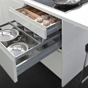 Nowoczesna zabudowa kuchenna z kolekcji Orlando K firmy Leicht. Miejsce na garnki i inne naczynie wydzielono w głębokiej szufladzie znajdującej się pod płytą grzejną. Wewnętrzną przestrzeń szafki organizuje praktyczny reling pozwalający zachować porządek.
