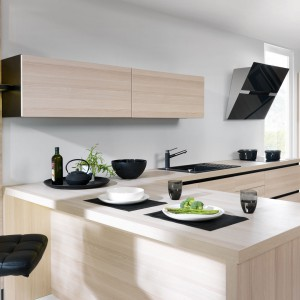 Zabudowa Emotion Augusto z oferty kuchni na wymiar Senso Kitchens firmy Black Red White. Połączenie drewna o chłodnej barwie ze szlachetną czernią to sprawdzony duet. Gładkie powierzchnie frontów odmierzone są liniami podziału korpusu – czarnymi metalowymi uchwytami – dyscyplinującymi układ.