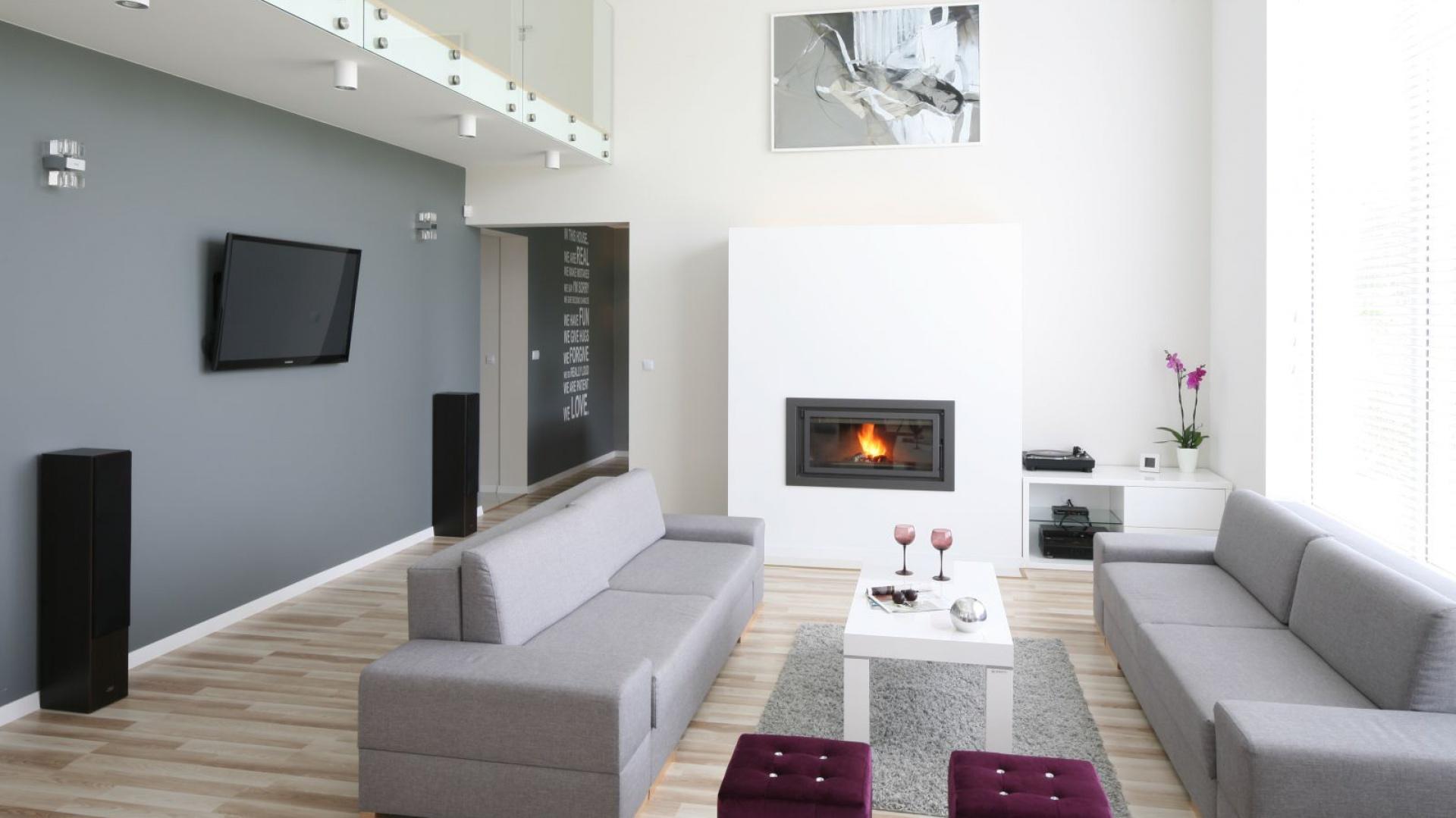 Szare, nowoczesne sofy i ściana, na której wisi telewizor wprowadzają do  przestronnego wnętrza wrażenie równowagi. Projekt: Karolina i Artur Urban. Fot. Bartosz Jarosz.