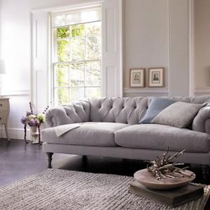 Szara, pikowana sofa oraz dywan w zbliżonej tonacji podkreślają elegancki wystrój wnętrza. Fot. Marks&Spencer.