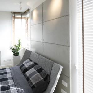 Szare tapicerowane łóżko dobrze prezentuje się na tle betonowej ściany. Proj. Agnieszka Ludwinowska. Fot.Bartosz Jarosz.