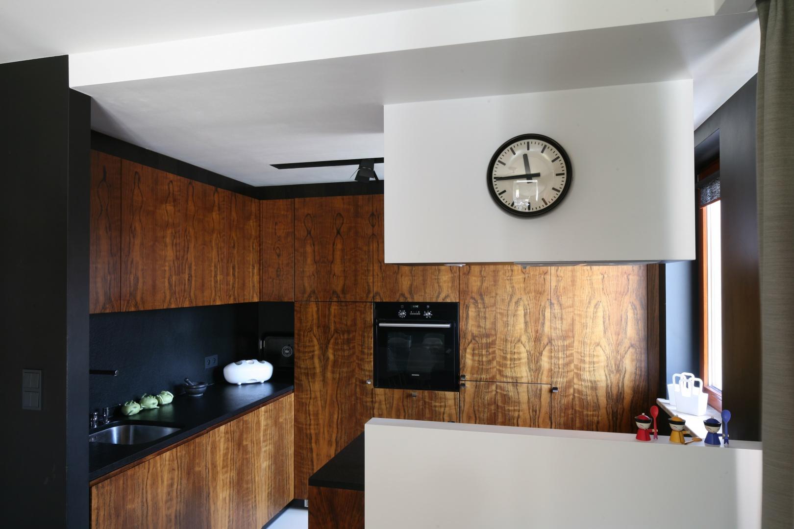 Wyspa została oderwana od podłogi. Bokiem oparta o ścianę nośną jest także przymocowana do ścianki działowej. Uniesiona na wys. 20 cm od posadzki wydaje się lżejsza, można też wygodnie sprzątać i myć podłogę. Projekt: Kasia i Michał Dudko. Fot. Bartosz Jarosz.