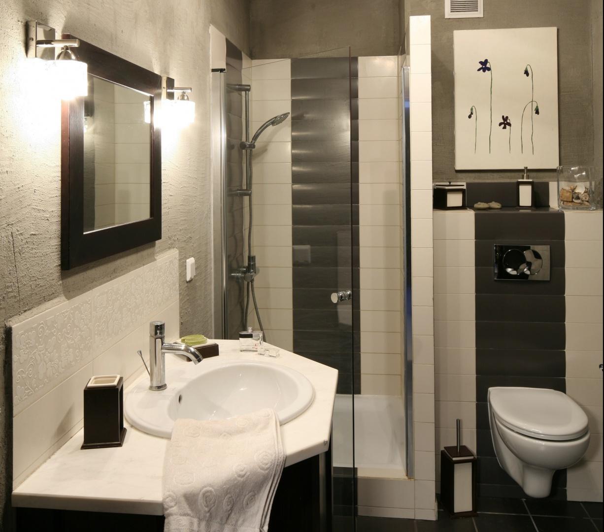 Utrzymana w minimalistycznych szarościach łazienka została urządzona w męskim, zdecydowanym stylu. Projekt Magdalena Kwiatkowska. Fot. Bartosz Jarosz.
