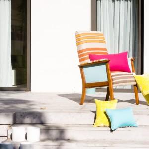 Fotel Wakacje z tkaniny na bazie juty, której pasy nadają całości leżakowego charakteru. Kolor stolarki w ciepłym odcieniu brązu ma przypominać odeskowanie pokładu jachtu, co podkreśla wakacyjny wygląd mebla. Fot. Deca.