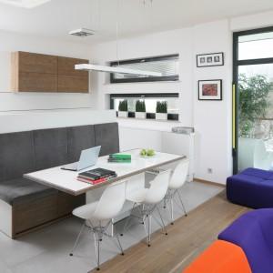 Strukturę i kolor drewna zastosowane na kuchennej zabudowie dopasowano o podłogi w salonie. Pozwolił to zachować stylistyczną spójność całej strefy dziennej. Projekt: Konrad Grodziński. Fot. Bartosz Jarosz. Stylizacja: Ewa Kozioł.