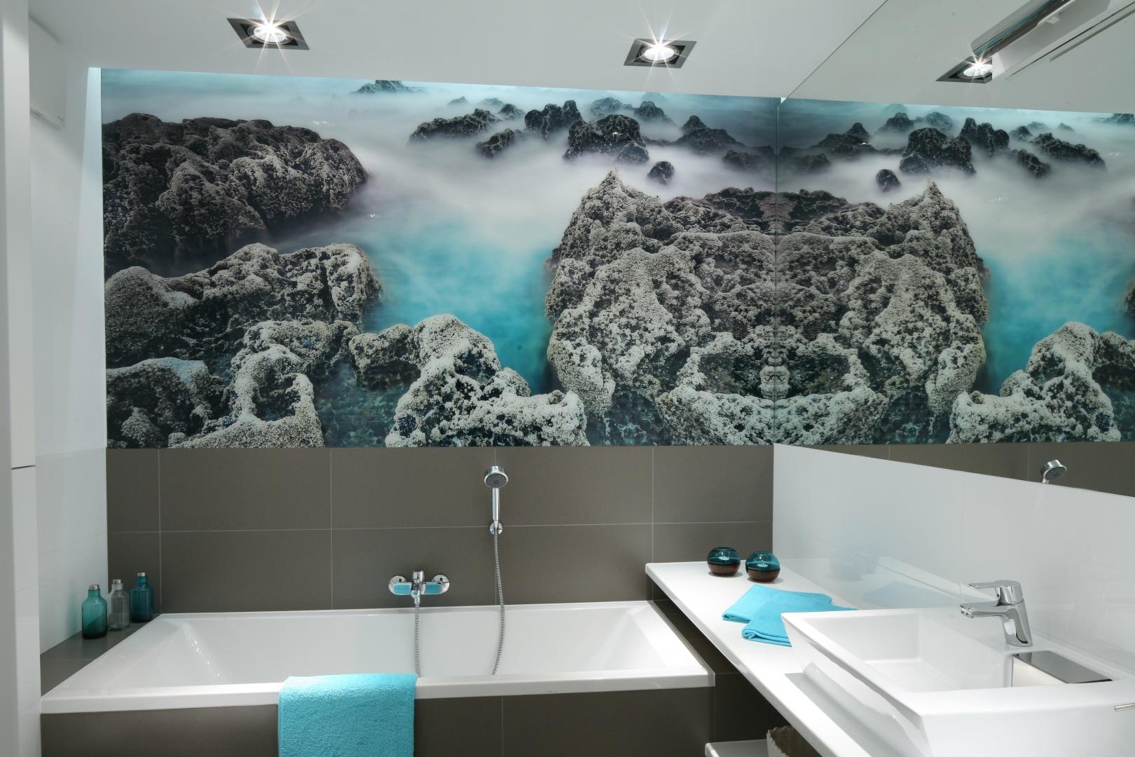 Główną ozdobę łazienki stanowi fototapeta ze zdjęciem z głębin oceanu. To do niej dobrano płytki ceramiczne w stonowanych kolorach – szarym oraz białym. Tylko tak subtelne barwy pozwoliły na właściwe jej wyeksponowanie. Projekt Anna Maria Sokołowska. Fot. Bartosz Jarosz.