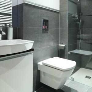 w niedużej łazience zrezygnowano z wanny na rzecz przestronnej kabiny prysznicowej. Minimalistkę wyposażenia podkreśla szary kolor okładzin ściennych. Projekt Marta Dąbrowska. Fot. Bartosz Jarosz.