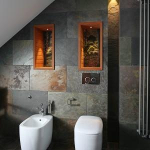 Mieniący się naturalnymi odcieniami łupek to prawdziwa ozdoba łazienki. Jego niepowtarzalny urok wyeksponowano poprzez zastosowanie różnorodnych źródeł światła – w tym umieszczonych w niszach nad sanitariatami. Projekt Katarzyna Koszałka. Fot. Bartosz Jarosz.