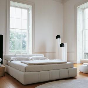 Jasne łóżko Tufty w zestawieniu z białymi ścianami oraz drewnianą podłogą, która ociepla wnętrze sypialni. Fot. B&B Italia.