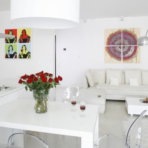 Otwarty salon, któremu towarzyszy kuchnia z jadalnią, jawi się jako czysta i neutralna przestrzeń. Jedyne barwne motywy tego wnętrza to silnie elektryzujący, abstrakcyjny obraz na płótnie zawieszony nad kanapą oraz plakat w stylu pop -artu na ścianie aneksu kuchennego. Projekt: Piotr Gierłatowski. Fot. Bartosz Jarosz.