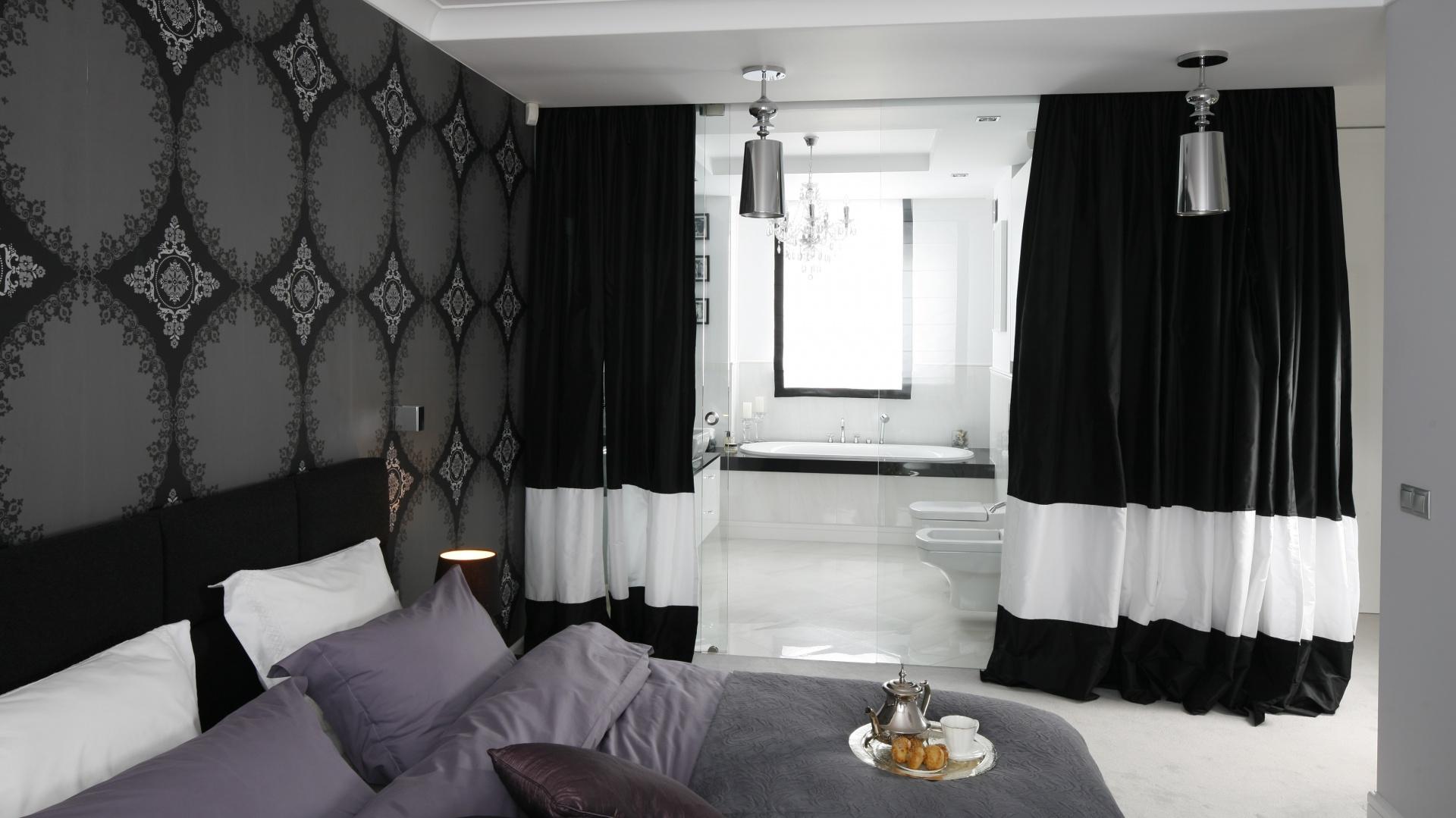 We wnętrzu granicę między strefą łazienkową i sypialnianą wyznacza tafla szkła oraz czarno – białe zasłony. Proj. Magdalena Smyk. Fot. Bartosz Jarosz.