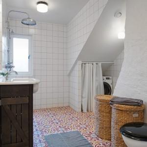 Połączenie kolorów i faktur w łazience nadaje jej stylowy charakter. Po prawej stronie znajduje się stary, odmalowany na biało komin, który tworzy we wnętrzu rustykalny klimat. Fot. Alvhem Makleri.