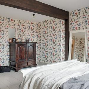 Dach w sypialni podtrzymują drewniane belki w intensywnym, ciemnym kolorze, korespondujące z kolorystyką starej komody. Tworzą umowny podział przestrzeni, gotowej do przyszłego wykorzystania. Fot. Alvhem Makleri.