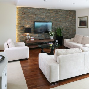Szykowny i funkcjonalny salon zaaranżowano z niezwykłą dbałością o proporcje między nowoczesnymi formami a neobarokowymi dodatkami. Urzeka on absolutną równowagą w łączeniu różnorodnych stylów, materiałów i form. Ciepło drewna (parkiet z drewna merbau) koresponduje z surowością kamienia (wykończona łupkiem ściana), a czystość form ograniczonych do minimum mebli współgra z finezyjnymi wzorami kanap. Projekt: Piotr Stanisz. Fot. Bartosz Jarosz.