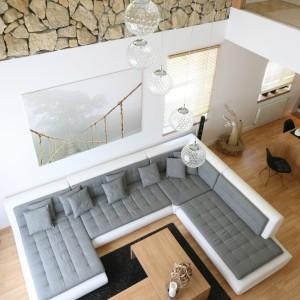 Salon ma wysokość dwóch kondygnacji. Jego ściany od połowy kondygnacji wykończono kamieniem, który wydobyto podczas renowacji budynku. Projekt: Małgorzata Błaszczak. Fot. Bartosz Jarosz.