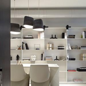 Wspólną ścianę kuchni i salonu w znacznej mierze zabudowano białymi, funkcjonalnymi półkami. Fot. Olga Akulova DESIGN.