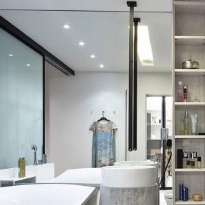 W łazience całą ścianę pokryto wielkoformatowym lustrem, w znaczący sposób powiększającym optycznie pomieszczenie. W centrum stoi designerska umywalka z sufitową baterią w kontrastującym z jasnym wnętrzem czarnym kolorze. Fot. Olga Akulova DESIGN.