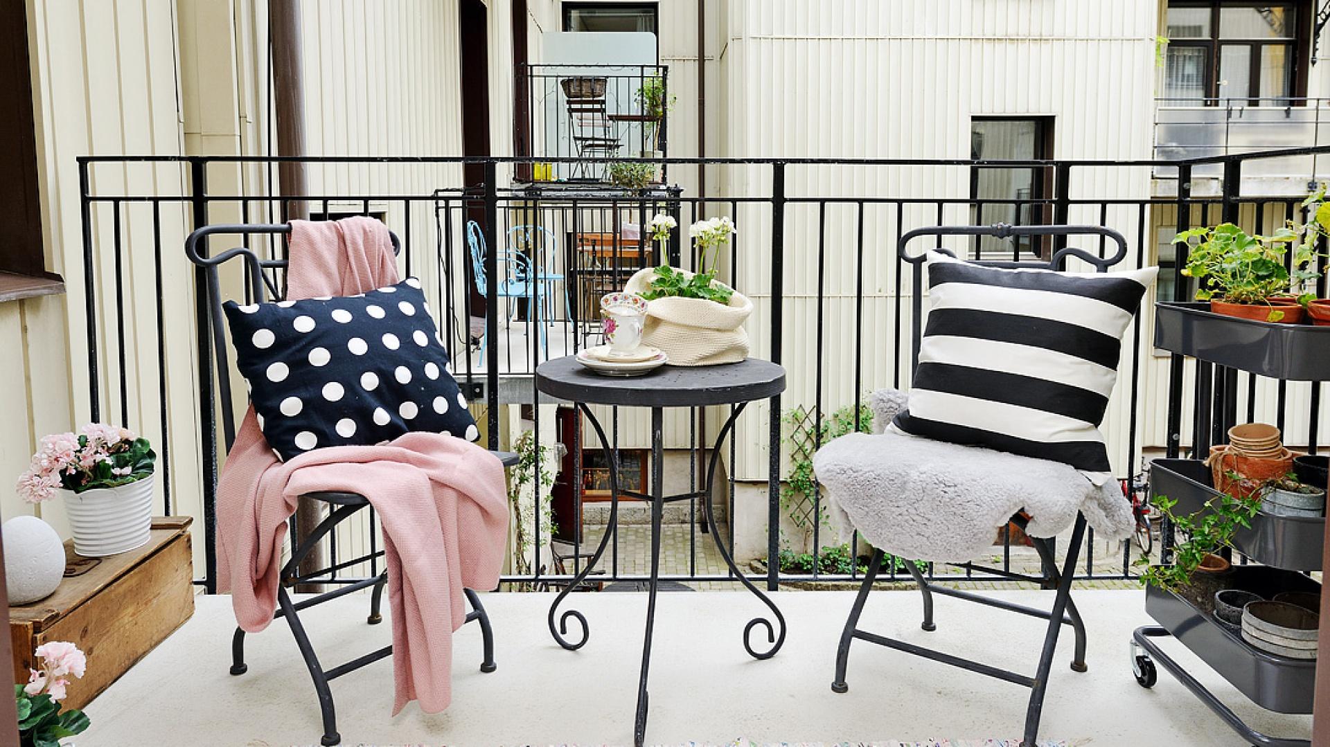Czarny, kuty stolik z dekoracyjnym wykończeniem stanowi ozdobę tarasu. Meble oraz balustrada tworzą przyjemny kontrast z jasną podłogą i jasnymi ścianami elewacji. Fot. Alvhem Makleri.