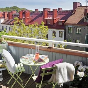Kolorowe meble ożywiają tarasową przestrzeń. Dzięki kolorowym poduchom w łatwy sposób możemy wprowadzić na balkon kolorystyczny akacent. Fot. Alvhem Makleri.