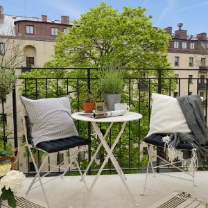 Dwa krzesła, stolik i wygodne, miękkie poduszki to obowiązkowy zestaw do wypoczynku na balkonie. Fot. Alvhem Makleri.
