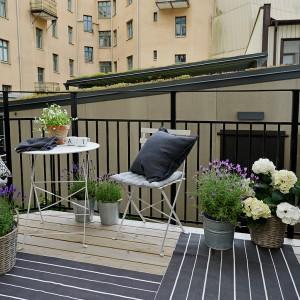 Na tym balkonie panuje kolorystyczna spójność. Na tarasowe deski ułożono ciemne dywany, które kolorystycznie nawiązują do dekoracyjnych poduszek. Fot. Alvhem Makleri.