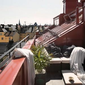 Na przestronnym tarasie wydzielono miejsce na siedzisko z wygodnymi poduchami oraz stolik kawowy. Rośliny umieszczone w doniczkach wprowadzają zieleń na taras. Fot, Fantastick Frank.