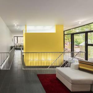 """Kolejny wyrazisty akcent we wnętrzu to żółte """"pudełko"""" zawieszone nad otworem w podłodze. Mieści się w nim wygodna, funkcjonalna łazienka. Projekt: Paul duBellet Kariouk, Kariouk Associates. Fot. Kariouk Associates."""