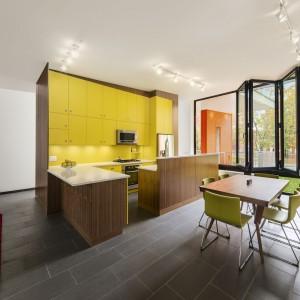 Najmocniejszym akcentem we wnętrzu są żółte szafki kuchenne wykonane na zamówienie. Pięknie ożywiają stonowany wystrój. Ciekawie prezentuje się również harmonijkowe okno. Projekt: Paul duBellet Kariouk, Kariouk Associates. Fot. Kariouk Associates.