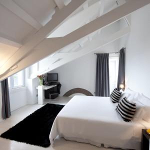 Białą sypialnię na poddaszu ożywiono czarnymi dodatkami. Ciemny dywan, zasłony i poduszki równoważą we wnętrzu biel ścian.Fot. Farol Hotel.