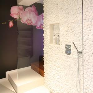 """Piękny storczyk nie tylko umila chwile relaksu w wannie, ale także dyskretnie """"zagląda"""" do strefy prysznica umilając kąpiel pod natryskiem. Prysznic typu walk-in oddzielony jest jedną szklaną taflą od reszty pomieszczenia. Ściana w całości wykończona białymi otoczakami oferuje praktyczną wnękę na kosmetyki. Fot. Bartosz Jarosz"""