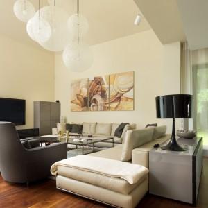 Proste formy szafek, klasyczne kanapy, a przy tym ciepła, jasna kolorystyka ścian sprawiają, że salon jest spokojny i stonowany - stworzony do odpoczynku. Ilość mebli i dekoracji ograniczono tak, by nie zabierać cennej dla właścicieli przestrzeni. Projekt: Tomasz Tubisz. Fot. Przemysław Andruk.