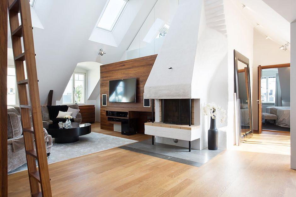 Rustykalny kominek, wyeksponowane drewniane belki stropowe, tradycyjny komplet wypoczynkowy i szklane elementy działowe na półpiętrze tworzą ciekawy wizualnie mariaż różnych stylów. Fot. Per Jansson