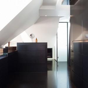 Obszerna garderoba została zabudowana pod sam sufit funkcjonalnymi szafami. Czarna podłoga i szafy kontrastują z białymi ścianami, tworząc wysmakowaną monochromatyczną kompozycję. Fot. Per Jansson