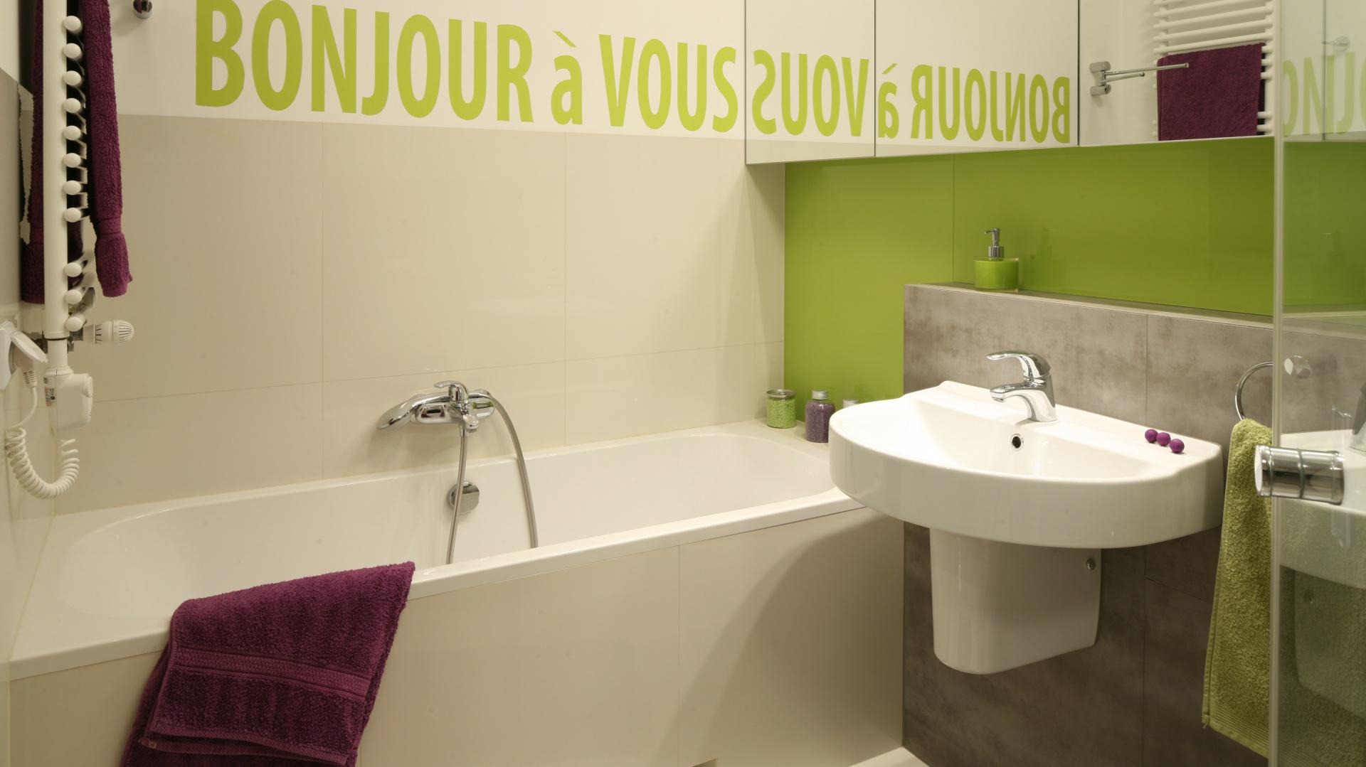 Na małej powierzchni łazienki dla czteroosobowej rodziny starannie wykorzystano każdy metr. Znalazło się tu miejsce zarówno na wannę, jak i kabinę prysznicową. Napis w zielonym kolorze w łazience dla rodziny właściciele namalowali własnoręcznie. Specjalny szablon, który ułatwił im pracę, zamówiono w agencji reklamowej. Projekt: Mart Kruk. Fot. Bartosz Jarosz